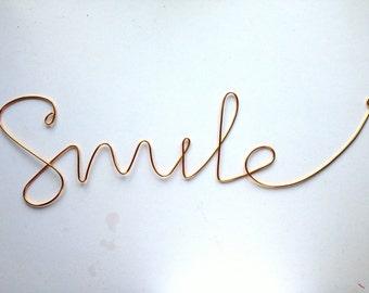 """Thick cursive """"Smile"""" wall phrase gold aluminium wire"""
