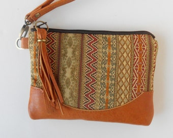 Wristlet or clutch in bohemian stripe with leather trim.
