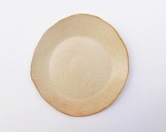 Medium-large sized speckled cream and orange-tinged ceramic serving plate