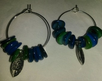 Hoop earrings featuring a leaf with the letter L and blue and green shells