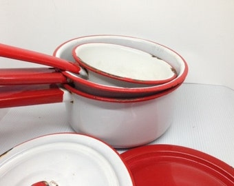 Group of White and Red Enamelware Pots, Pans, and Lids