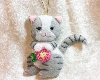 Grey tabby cat with pink flower