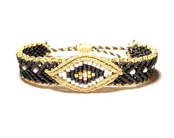 Black band bracelet with gold evil eye