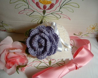Handmade crochet hat for baby girl executed in white wool with a purple rose applied. Crochet baby fashion romantic and feminine