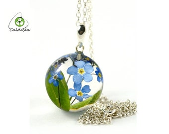 Pendant with real forget-me-not flowers (Myosotis sylvatica) with leaves in the resin sphere on a silver chain. Sphere 2.5 cm. Chain 45 cm.