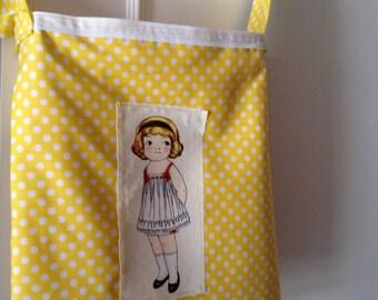 A yellow polka dot bag with vintage doll print- medium size