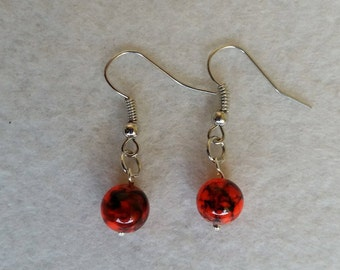 Sterling silver earrings with orange glass drawbench beads.