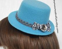 Blue mini top hat fascinator with zebra bow, lace trim, and rhinestone