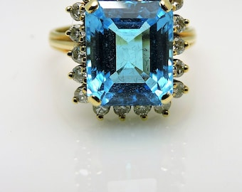 Lady's Yellow 14 Karat  Ring Size 8.75 With One 11.00Ct Retangular  Blue  Topaz And 18=0.46Tw Round Diamonds