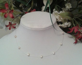 Romantic feminine necklace of small salt water pearls strung on clear filiment with silver tone clasp. Perfect for petite woman or teen .
