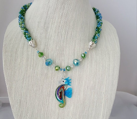 Green and blue beaded kumihimo woven necklace with glass seahorse pendant