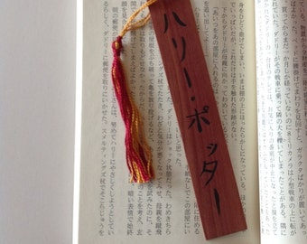 Harry Potter in Japanese calligraphy on a wooden bookmark with gryffindor colors