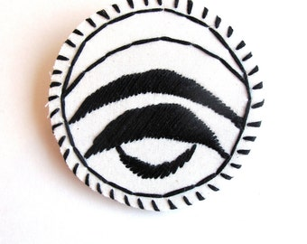 Geometric textile brooch hand embroidered in black and cream on cream muslin with a cream felt backing An Astrid Endeavor