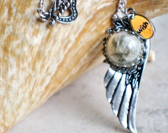 Dandelion seed wishes on angel wing pendant.