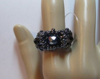 Ring with black hematite oblong seed beads with black AB rondelle crystals on stretchy cord size 8