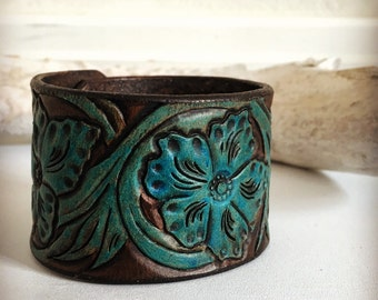 Leather cuff bracelet with turquoise flower desgin on brown background