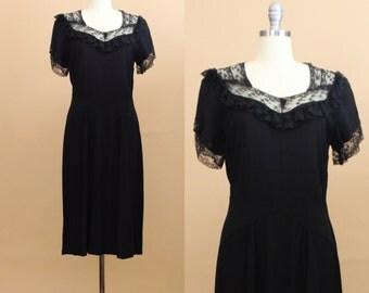 1940s. black silk crepe dress with lace illusion neckline. size medium