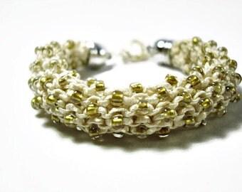 Knitted bracelet. Cream color bracelet in shiny ribbon yarn and Toho beads, fiber jewelry, statement bracelet, Christmas gift