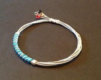 A handmade recycled guitar string bracelet/bangle