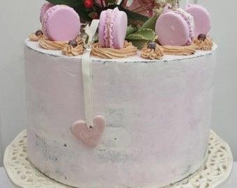 Pink chocolate semi-naked fake cake with fake strawberry and caramel macaroons,
