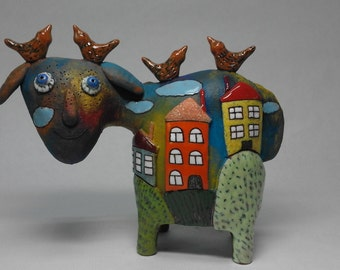 Sculpture sheep with houses and birds