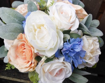 Natural ivory, blue and peach wedding bouquet. Made with a mix of artificial roses, peonies, delphinium and greenery.