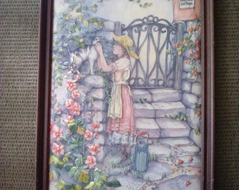 Framed Needlepoint Textile Of A Girl And Her Cat Outside A Cottage