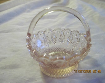 small pink depression glass basket with handle and scalloped rim