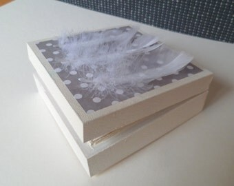 square box , wooden , gray origami paper with white spots , white feathers