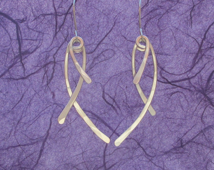 Lightly hammered sterling silver dangle earrings shaped in the symbol of the fish