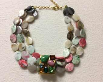Fancy oval pebbles necklace with big center ring with multicolored stones and crystals and various forms