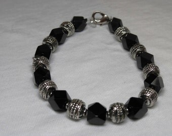 Black and silver bracelet has an elegant touch with faceted cube black beads. #B 0009-15