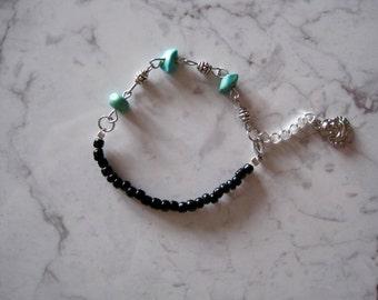 Turquoise stone bracelet with black beads.