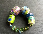 Handmade lampwork glass bead set by Lori Lochner mosaic violets chartreus and purple artisan jewelry making and textile design supply