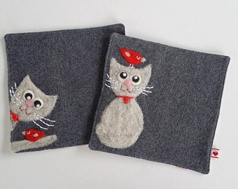 Set of two dark gray wool fabric coasters with needle felted light gray kitty cat and red birdie bird