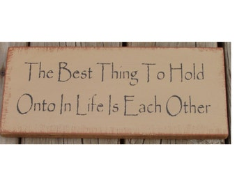 The best thing to hold onto in life is eachother primitive wood sign