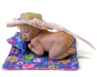 "Doll 4"" sleeping baby cast in porcelain wearing nothing but her birthday suit and Easter bonnet and comes wth tiny quilt and pillow"