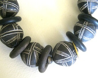 large clay beads... made in mali, these tribal elements are very handsome..incised surface design