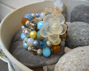 Boho Style Multi Strand Light Blue Turquoise Topaz Antique Brass and Cream Beaded Memory Wire Bracelet with Frosted Cream Rose Button Focal