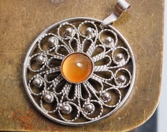 Vintage round silver tone metal filigree pendant with glass stone