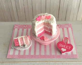 "Miniature Pink Valentine Layer Cake, A Slice Of Cake, And A Little Hanging Heart Sign That Says ""SWEET"""