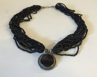 Glass seed bead necklace with silver and jet black medallion.