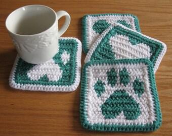 Crochet Coasters. Jade and white coaster set with dog paw prints and hearts. Pet lover mug rug