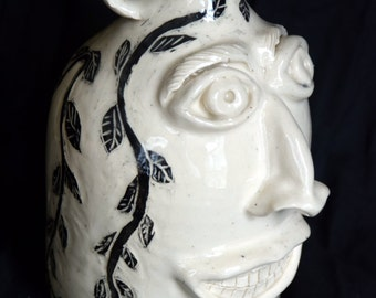 face jug with hand decoration