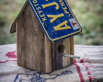 License plate birdhouse built from reclaimed wood and vintage license plates.