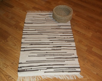 Hand-woven Rag Rug made entirely of recycled tee shirts plus a tee shirt sheet, with a color palette of cream, tan, and brown.