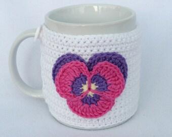 White  crochet mug cozy with applique pansy.