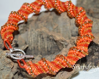 Cellini spiral bracelet in hot orang, reds and golds finished with a sterling silver toggle clasp.