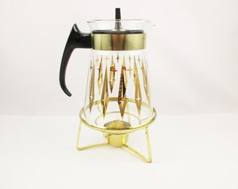 A 'Pyrex' Carafe With Black Cap - Gold Diamond and Star Pattern - Glass Hot or Cold Carafe - Warmer Base on Hairpin Legs - 8 Cup Carafe
