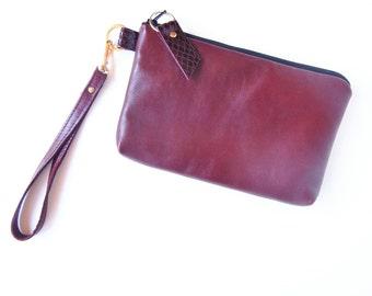 Burgundy leather wristlet or clutch.